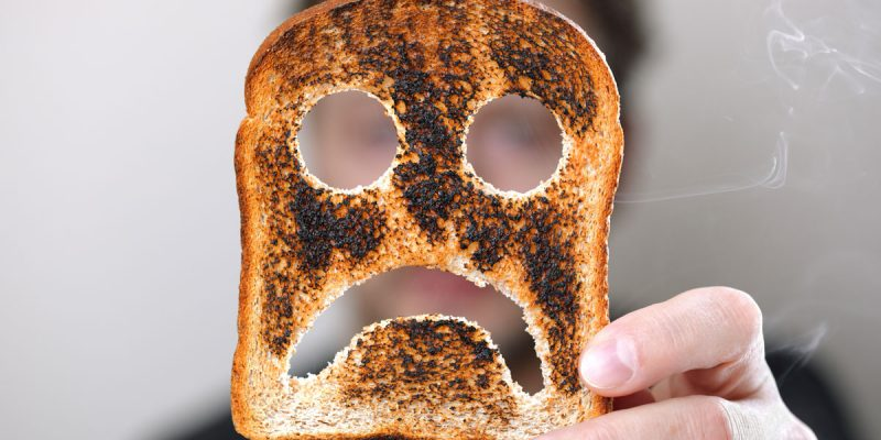 Person Holding a Piece of Toast with Frown